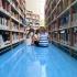 bambini seduti per terra nei corridoi tra gli scaffali dei libri